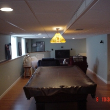 wood flooring custom pool room with tv and chairs